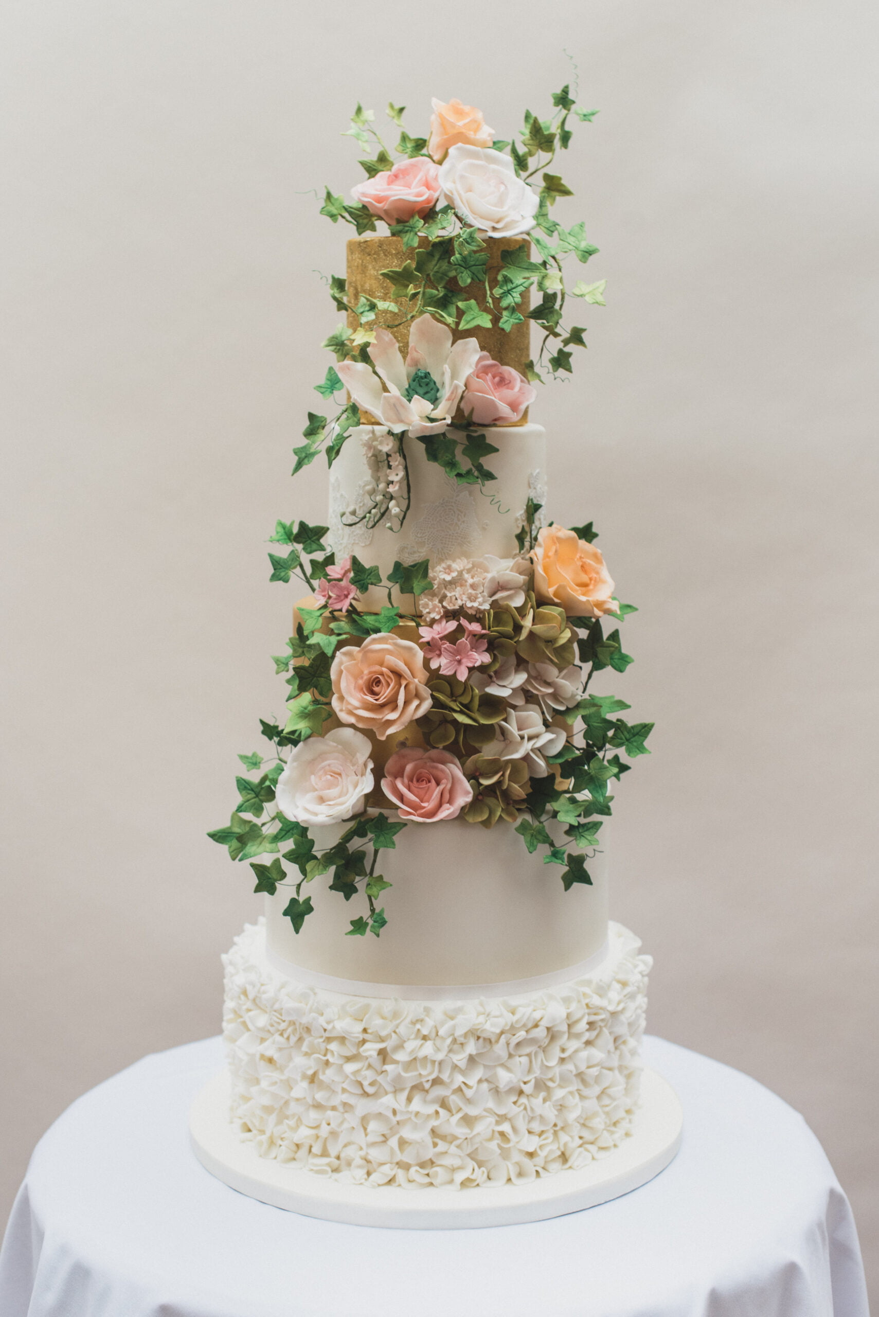 5 tier shows topping wedding cake finished with gold paint, ivory handmade ruffles, handmade sumptuous pastel sugar flowers designed by Bluebell Kitchen