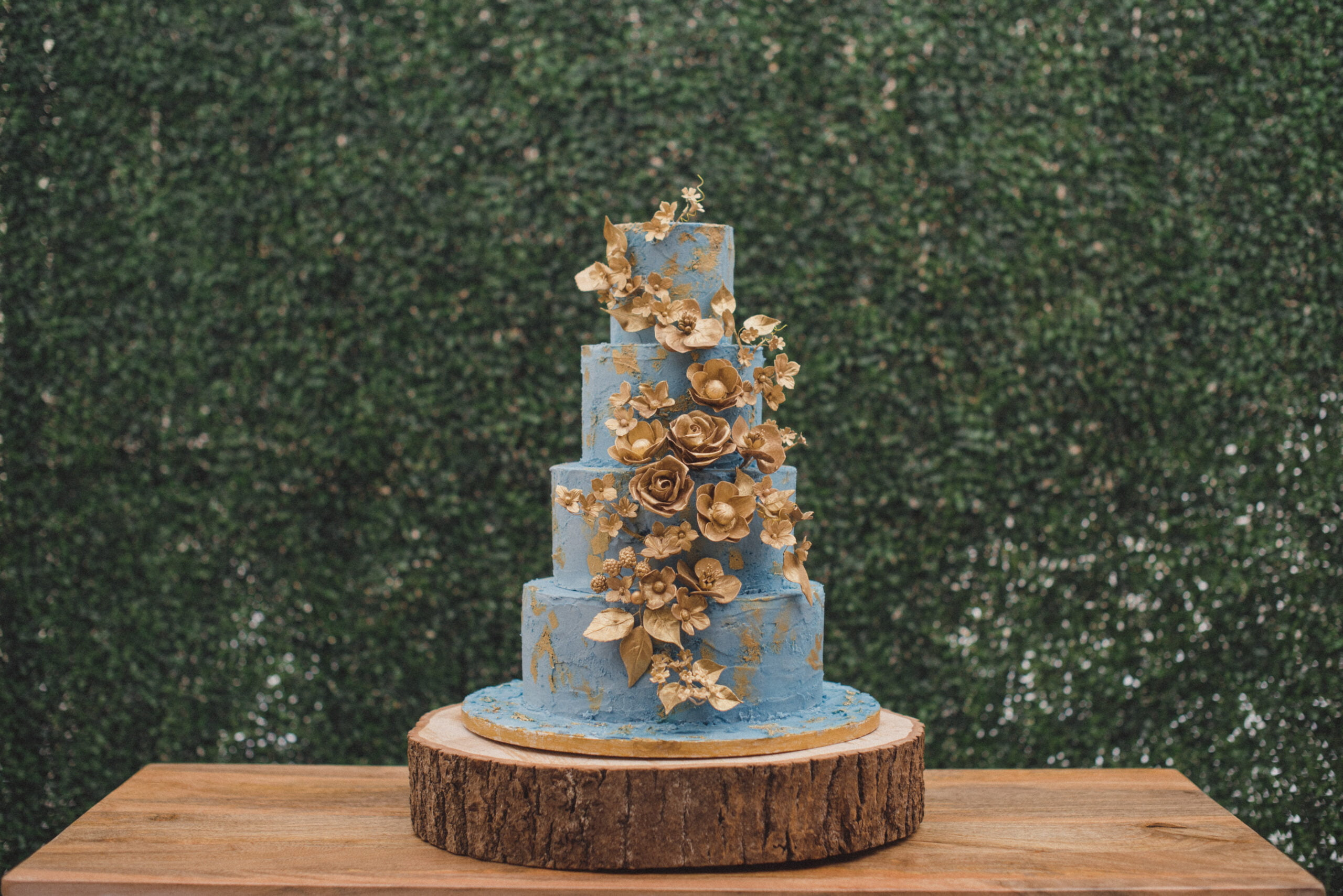 Cornflower blue buttercream wedding cake finished with gold painted elements and handmade gold painted sugar flowers designed by Bluebell Kitchen