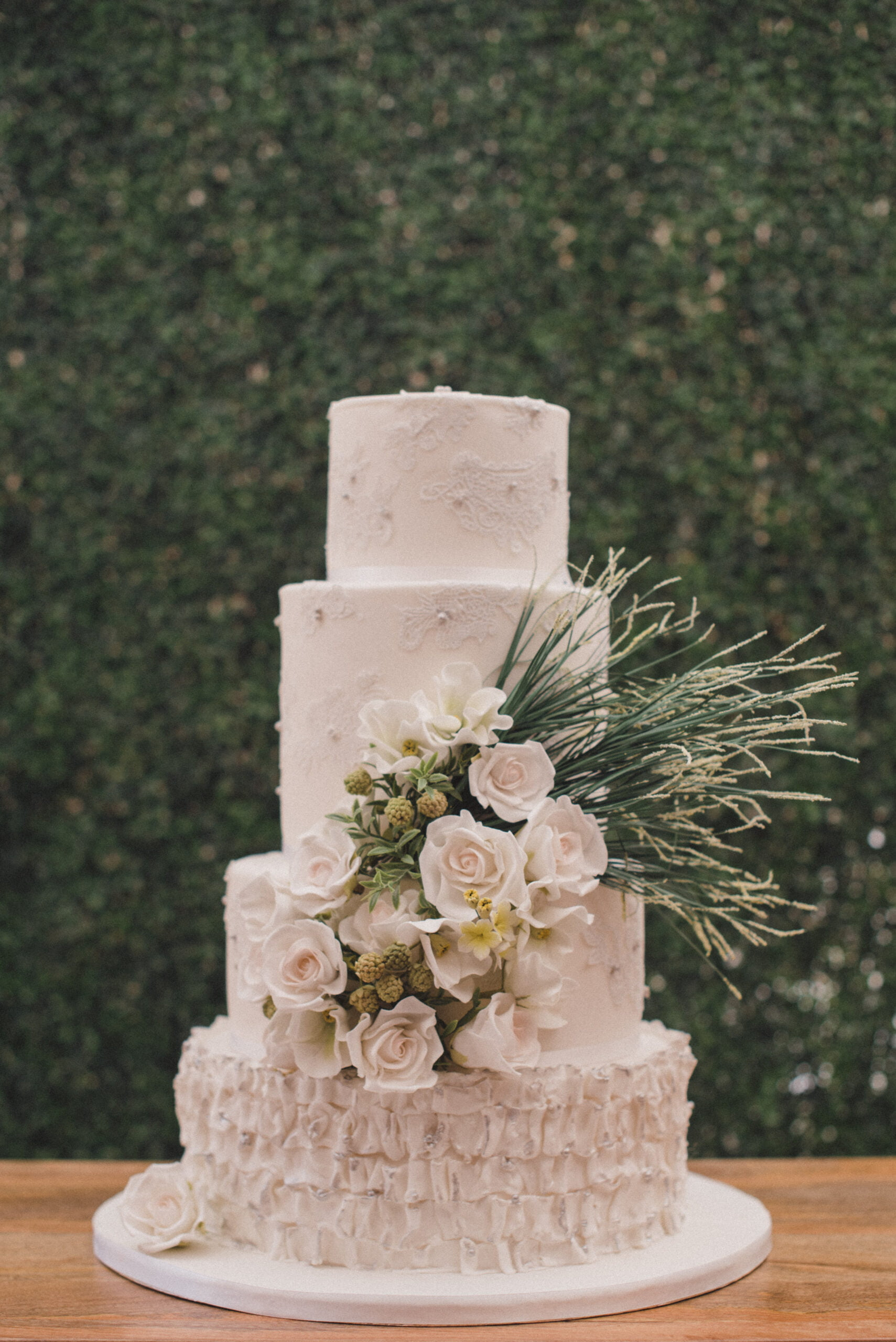 White wedding cake finished with delicate edible lace, handmade sugar ruffles and handmade white sugar roses designed by Bluebell Kitchen