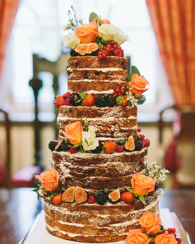 Naked Wedding Cake filled with summer berries fruit and peach and ivory roses