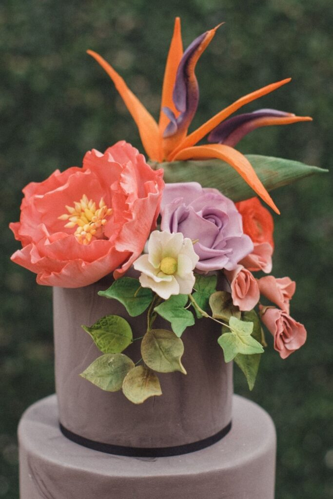 Bold and bright Bird of Paradise sugar flowers on a deep grey marble wedding cake
