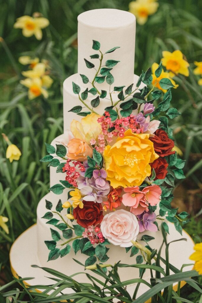 Bright, bold sugar flowers including sunshine yellow peonies, deep red roses, hint of pink roses and lots of ruscus leaves