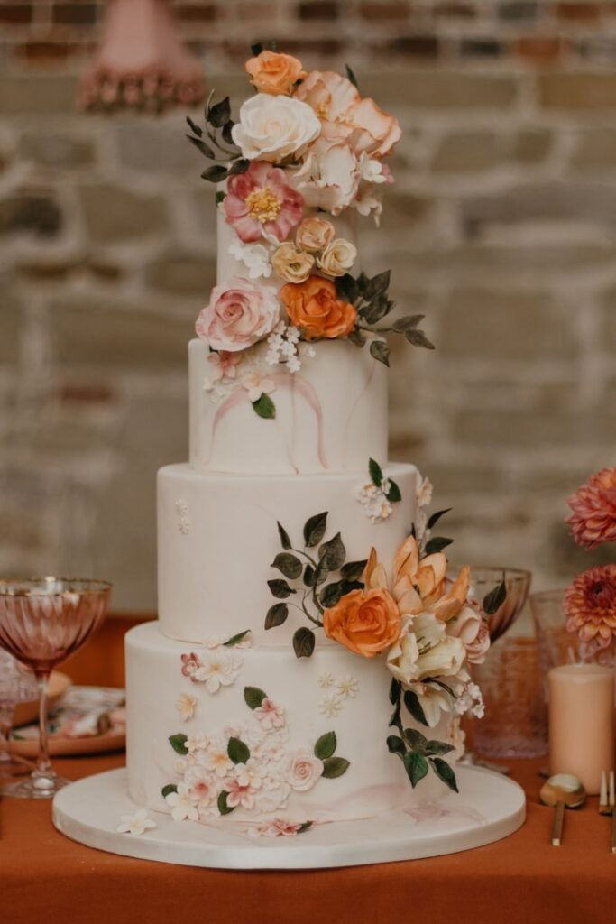 Handmade pastel peach and ivory sugar flowers wedding cake finished with blush pink marble fondant for bohemian wedding at Chiddinstone Castle