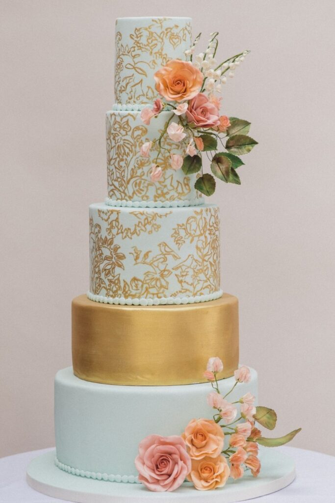Pastel Pink Sugar Roses on a five tier mint green wedding cake with gold texture painting