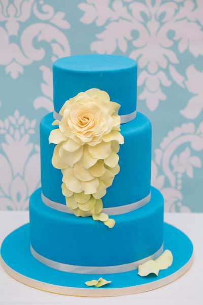 Three tier blue cake with cascade of flowers