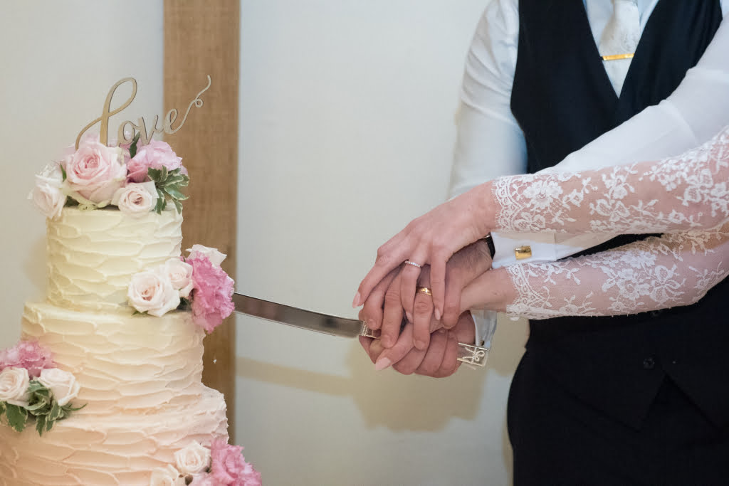 Couple cutting their textured buttercream pink ombre wedding cake