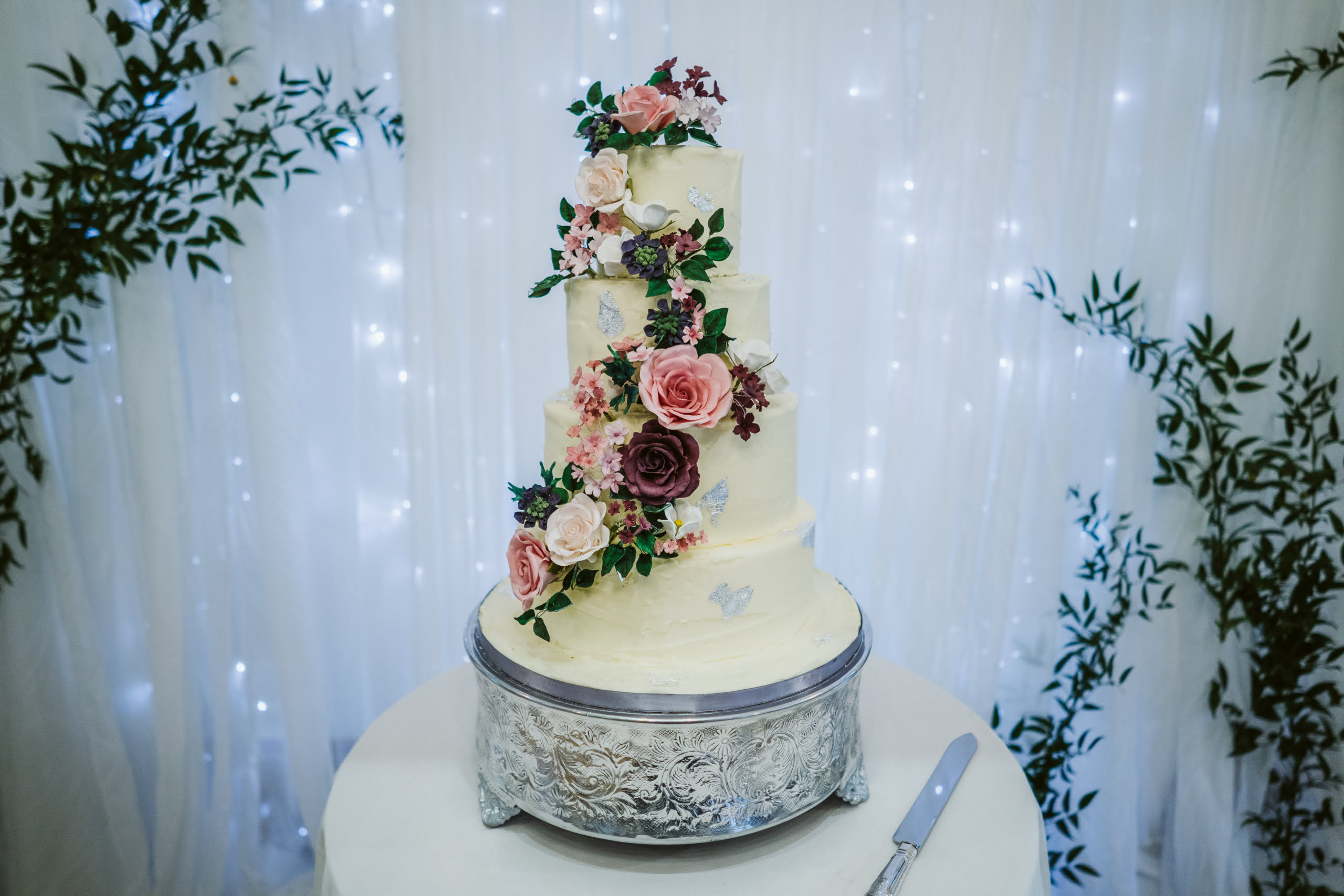 Handmade pink and burgundy sugar flowers cascade down a buttercream silk leaf 4 tier wedding cake