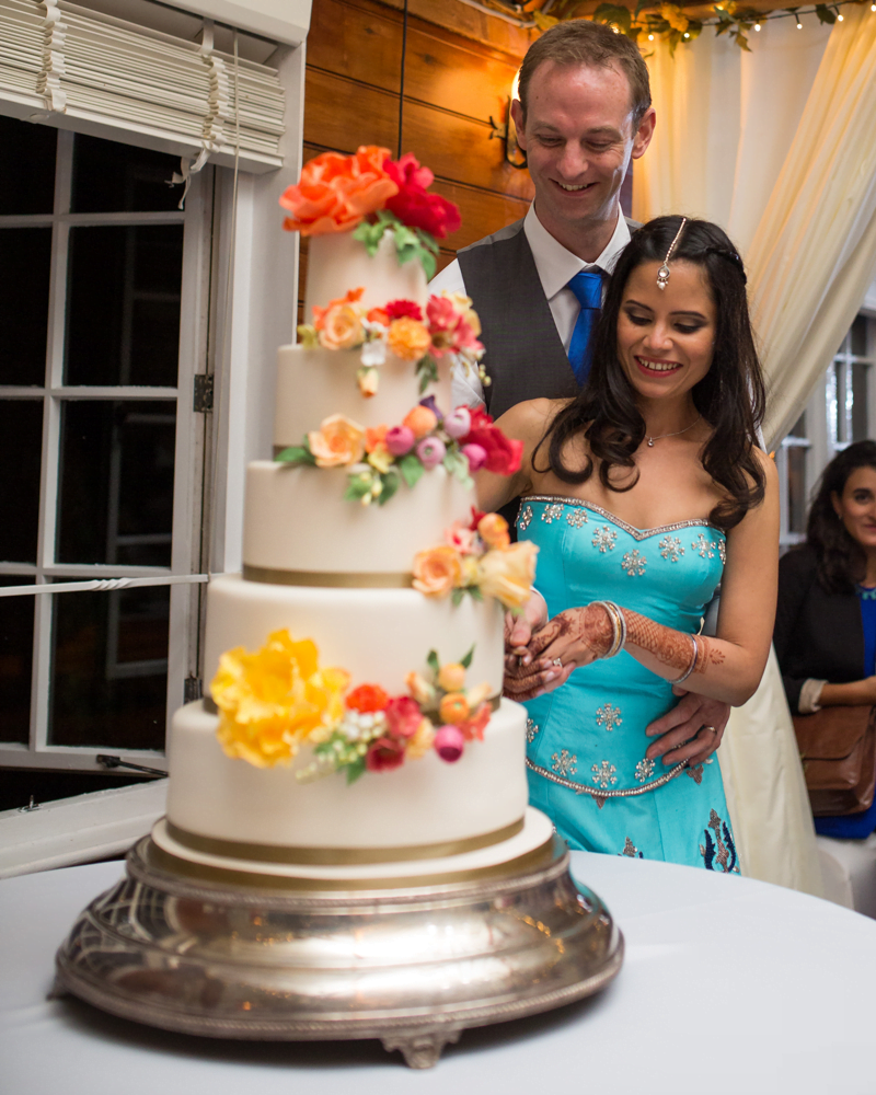 Couple cutting with bright and bold sugar flower wedding cake