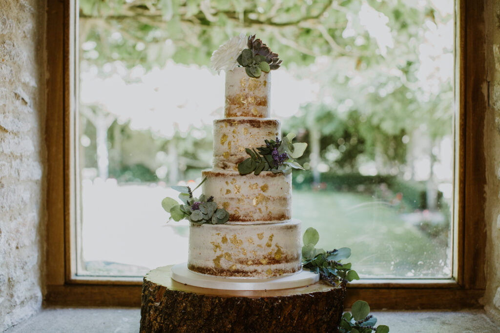 Nearly Naked Wedding Cake finished with roses, succulents and eucalyptus