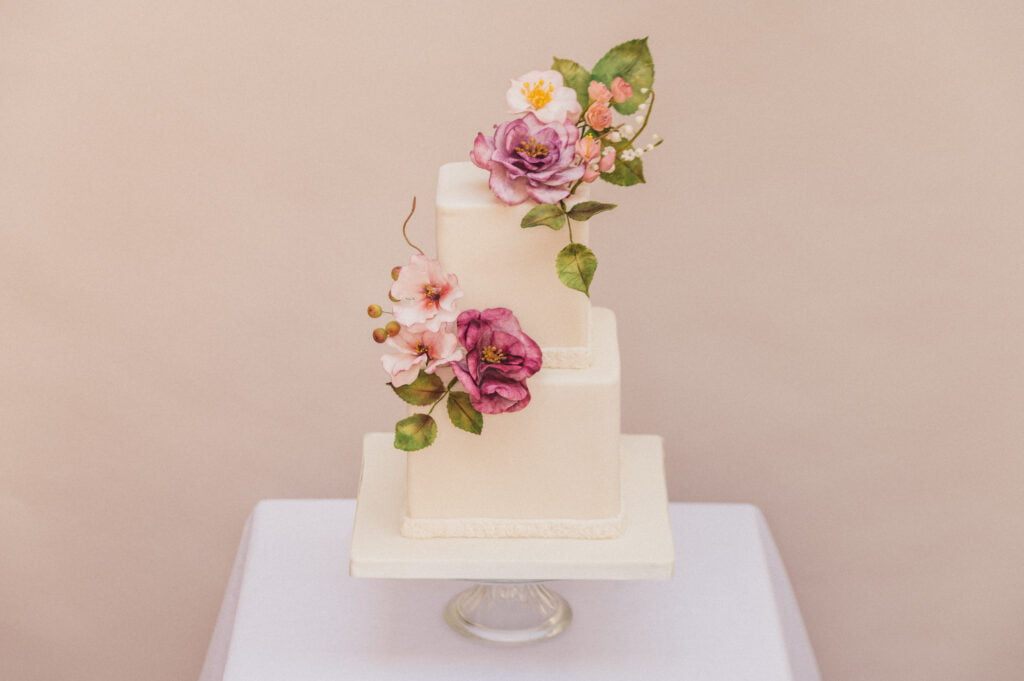 Two tier micro wedding cake with handmade lilac sugar flowers designed by Bluebell Kitchen