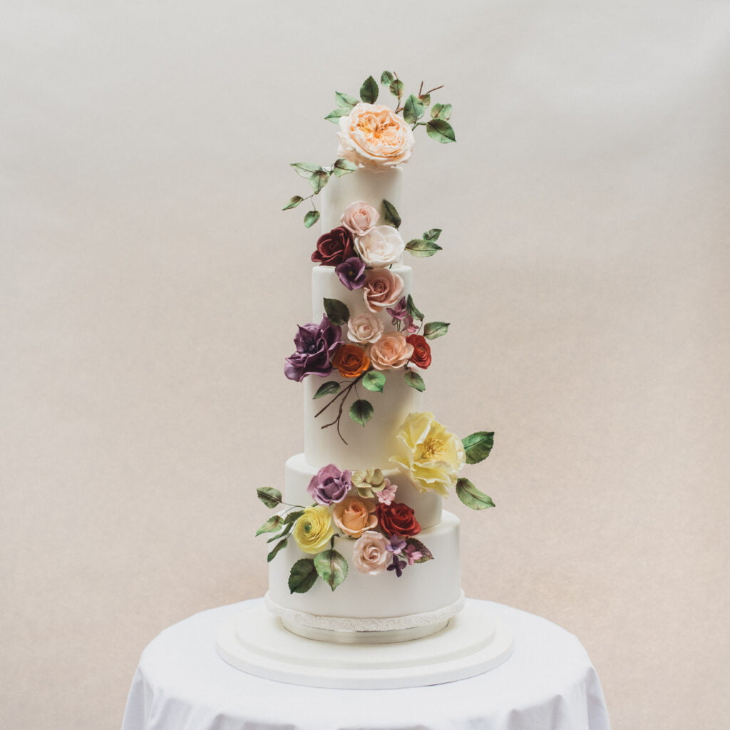Five tier white fondant iced wedding cake filled with handmade sugar flowers