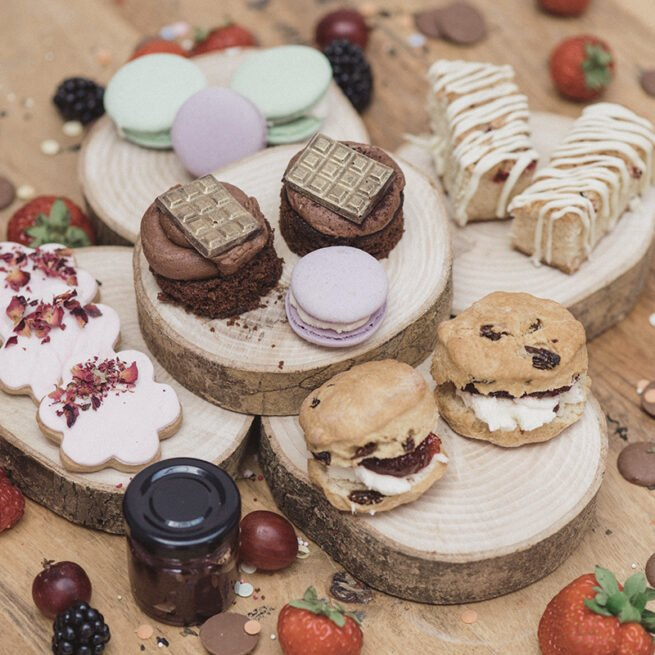 Afternoon Tea at Home: selection of sweet treats includes homemade scones filled with delicious homemade jam, chocolate sponges, mouth-watering macarons, rose petal cookies and white chocolate & raspberry blondies
