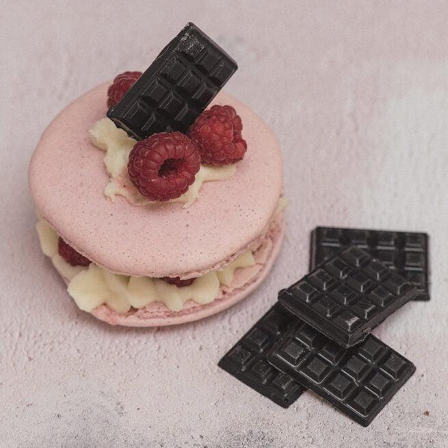 Handmade gourmet giant dusky pink macaron filled with fresh raspberry cream and handmade dark chocolates