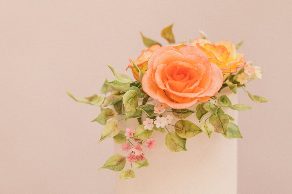 Single tier wedding cake with exquisite orange and yellow handmade sugar roses and greenery