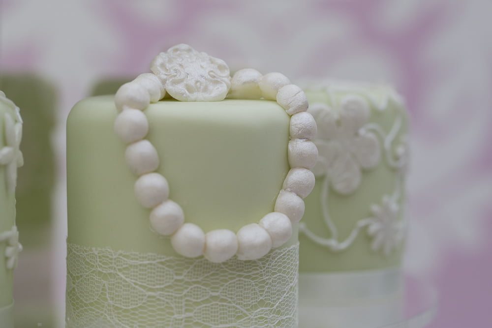Mint green mini wedding cakes with handmade pearls and lace