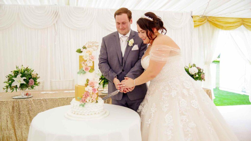 Couple cutting their centre piece gold textured sugar flower filled wedding cake