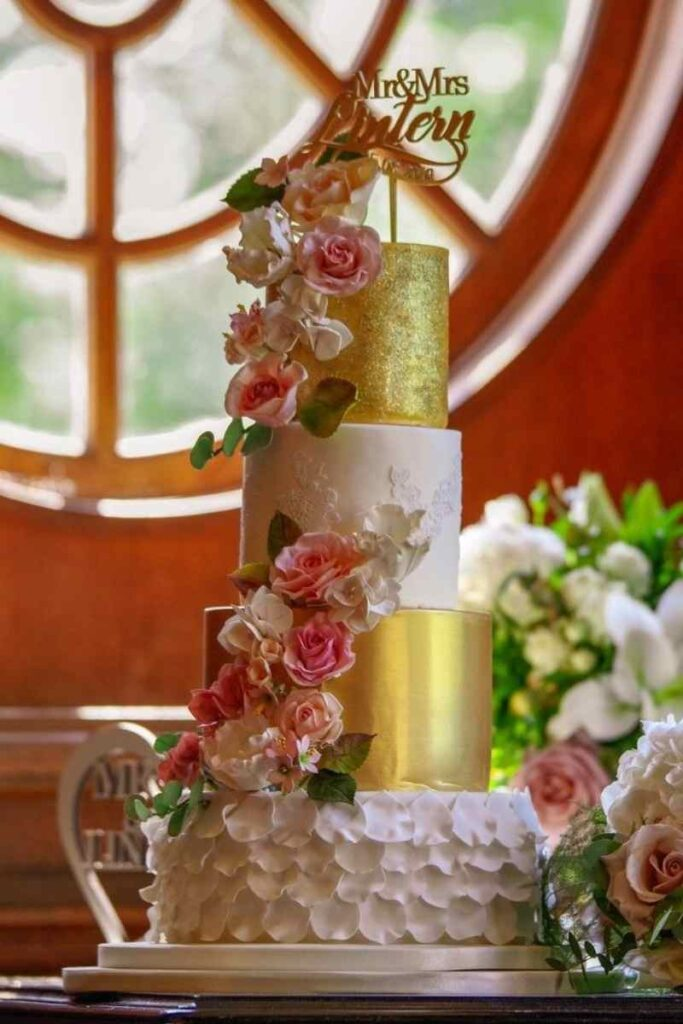 Four Tier Gold Lace Textured Wedding cake filled with sugar flowers in blush pink and ivory