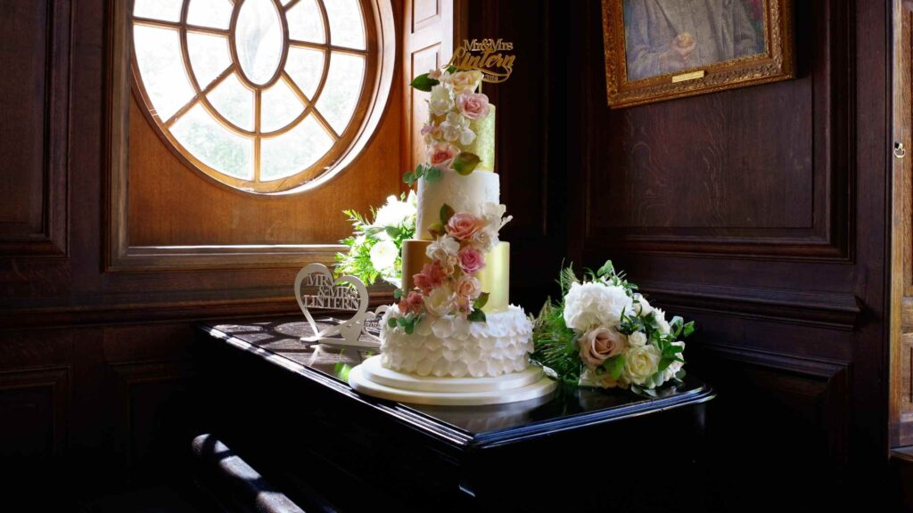 Four Tier ivory and gold textured wedding cake on the grand piano at Bradbourne House