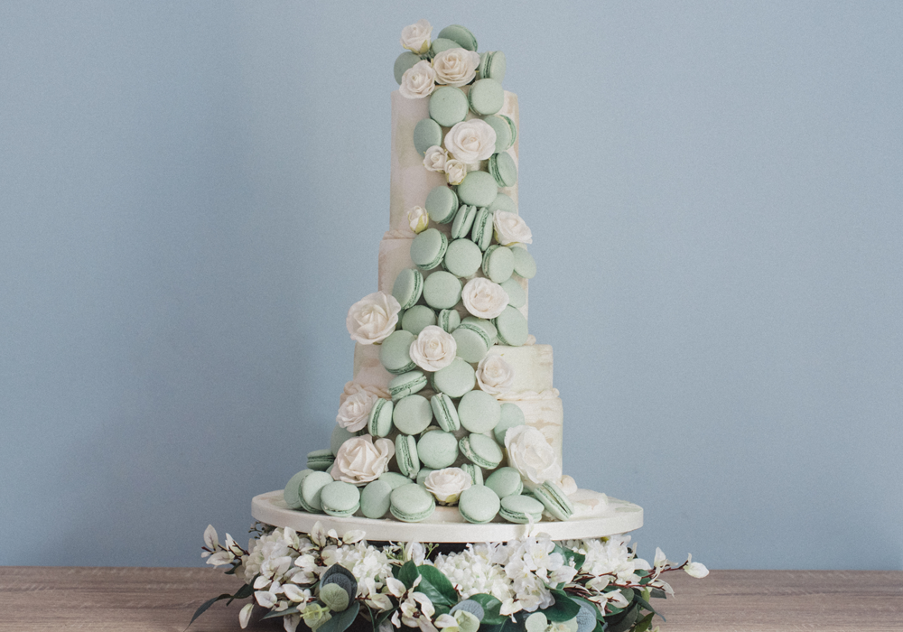 Mint Green Macaron waterfall flowing down a 4 tier cake with extra white sugar roses
